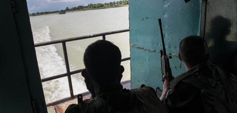 Myanmar-soldiers-ride-on-a-boat-tra
