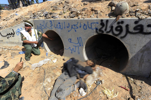 "A Libyan National Transitional Council (NTC) fighter looks through a large concrete pipe where ousted Libyan leader  Moamer Kadhafi was allegedly captured, with a dead loyalist gunman in the foreground, in the coastal Libyan city of Sirte on October 20, 2011.  A Libyan National Transitional Council (NTC) commander had told AFP that Kadhafi was captured as his hometown Sirte was falling, adding that the ousted strongman was badly wounded.  Arabic graffiti in blue reads: ""This is the place of Kadhafi, the rat.. God is the greatest.""   AFP PHOTO/PHILIPPE DESMAZES"