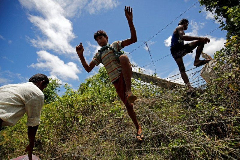 A Rohingya boy jumps over the border fence to enter inside Bangladesh border, in Cox's Bazar, Bangladesh, August 27, 2017. REUTERS/Mohammad Ponir Hossain