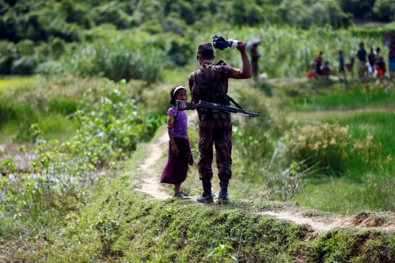 A member of Border Guard Bangladesh (BGB) tells a Rohingya girl not to come on Bangladesh side, in Cox's Bazar, Bangladesh, August 27, 2017. REUTERS/Mohammad Ponir Hossain