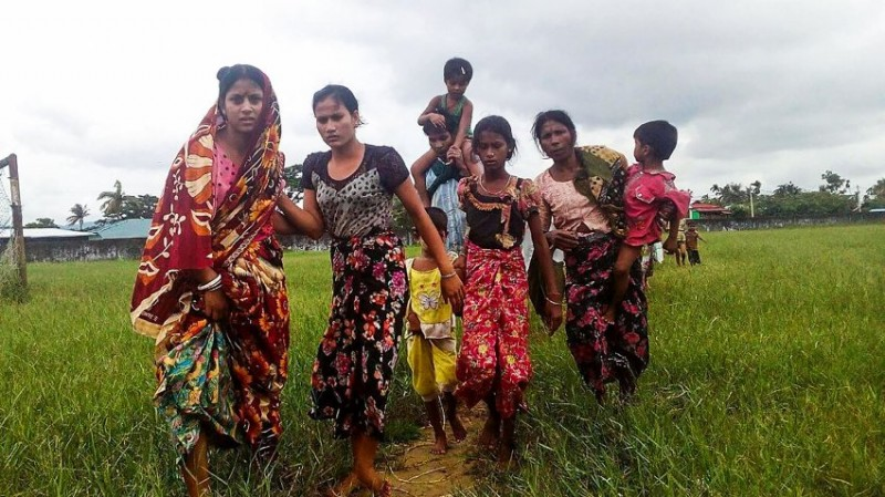 Women and children fleeing violence in their villages arrive at the Yathae Taung township in Rakhine State in Myanmar on August 26, 2017. Terrified civilians tried to flee remote villages in Myanmar's northern Rakhine State for Bangladesh on August 26 afternoon, as clashes which have killed scores continued between suspected Rohingya militants and Myanmar security forces. / AFP PHOTO / Wai Moe